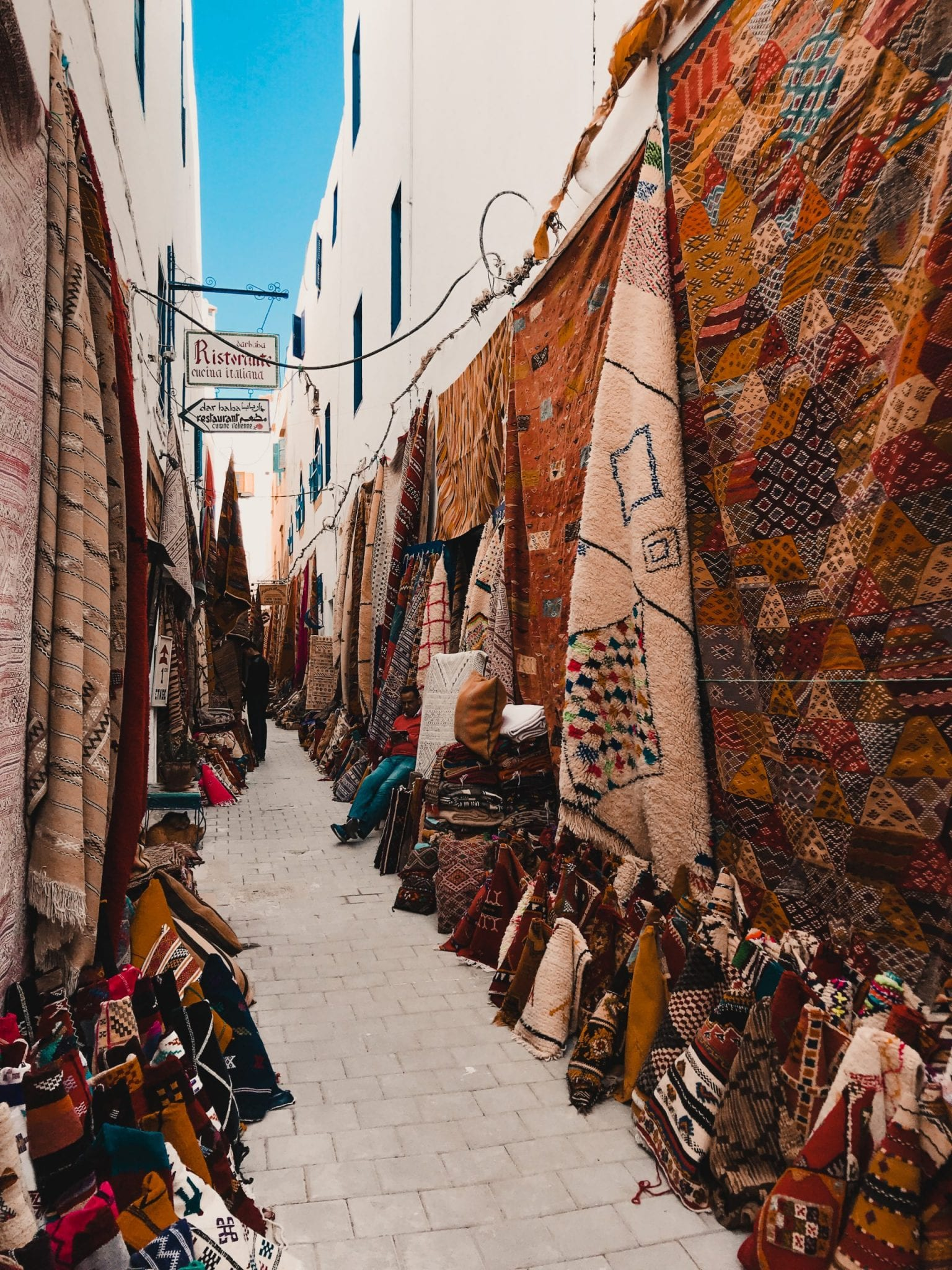 Rugs and textiles in an alleyway, Essaouira Morocco